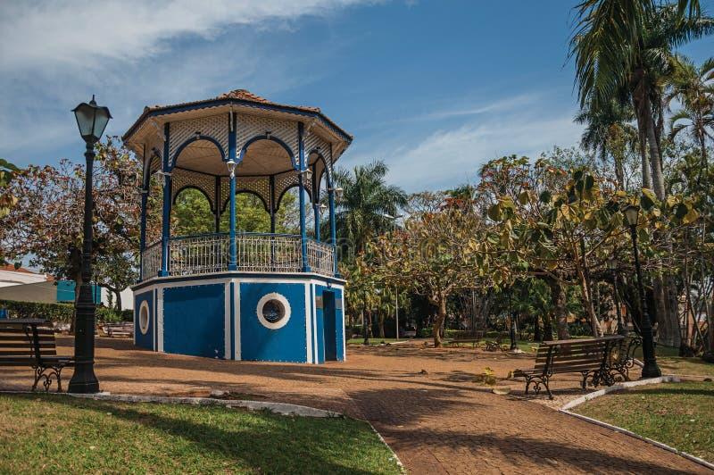 Stary kolorowy gazebo i oświetleniowy słup po środku zielenisty ogrodowy pełnego drzewa, w słonecznym dniu przy São Manuel obraz stock