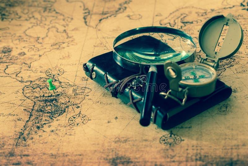 Stary kompas ze szkÅ'a powiÄ™kszajÄ…cego i notebookiem leżącym na starej mapie zdjęcia royalty free