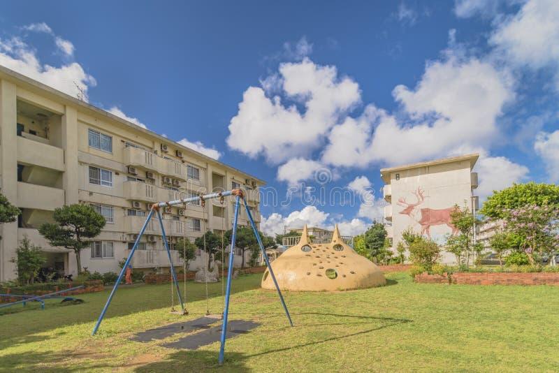 Stary kompleks mieszkaniowy z huśtawki i dzieci grami w pobliżu Amerykańskiej wioski w Okinawa, dokąd zwierzęta lubią dee obrazy stock