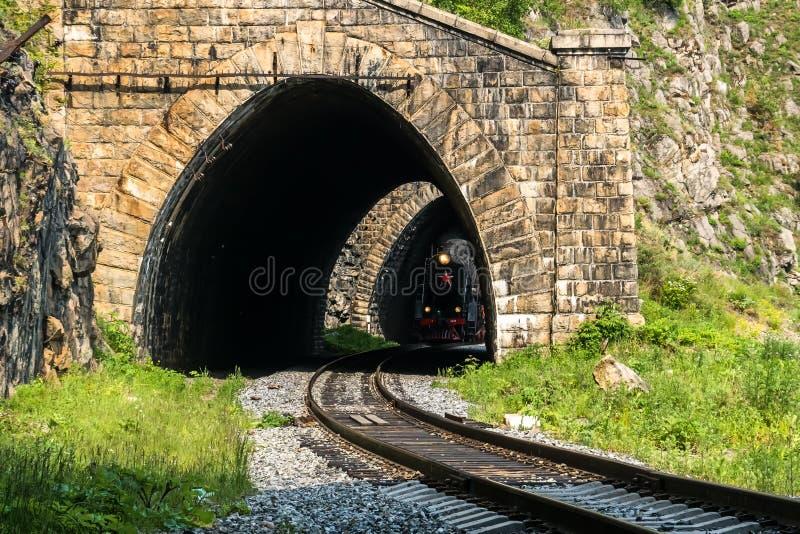 Stary kontrpara pociąg opuszcza tunel na Baikal kolei obraz royalty free