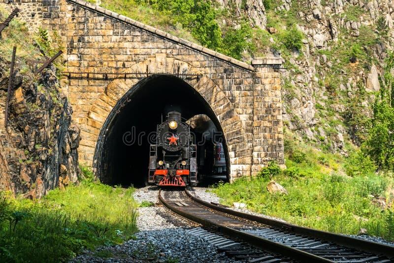 Stary kontrpara pociąg opuszcza tunel na Baikal kolei obraz stock