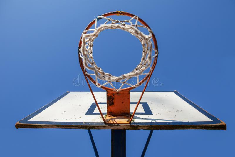 Stary koszykówka obręcz Przeciw niebieskiemu niebu Spod Spodu zdjęcie stock