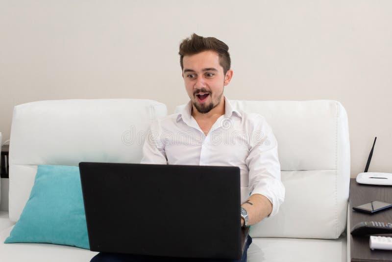 stary laptopa Przystojny biznesmen pracuje z laptopem w biurze Szczęśliwy młody człowiek w białym koszulowym obsiadaniu na kanapi obraz stock