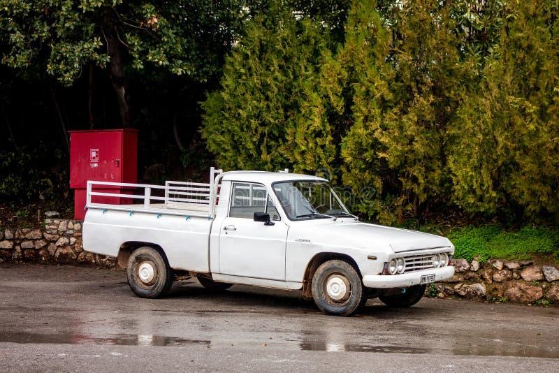 Stary legendarny vintage Mazda B1600 pickup zaparkowany na mokrej drodze przed drzewami w Grecji, gdzie te japońskie pojazdy zdjęcie royalty free