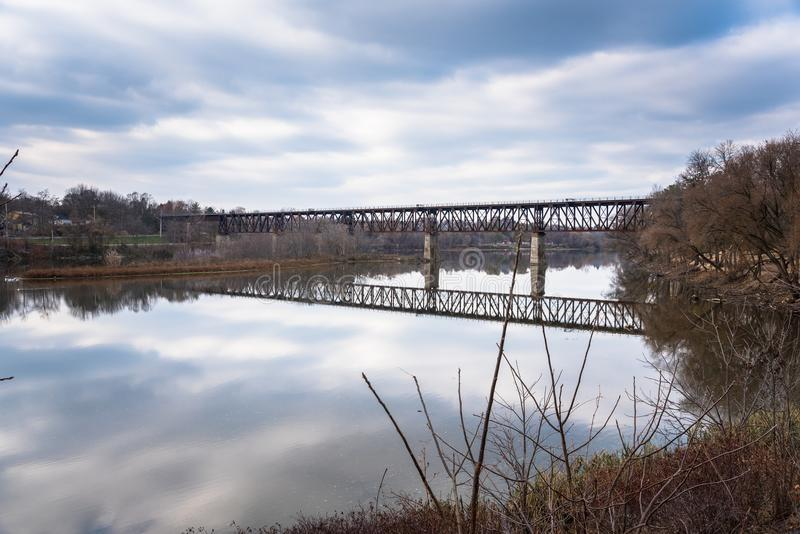 Stary linia kolejowa most nad Chmurnym niebem i rzeką fotografia royalty free