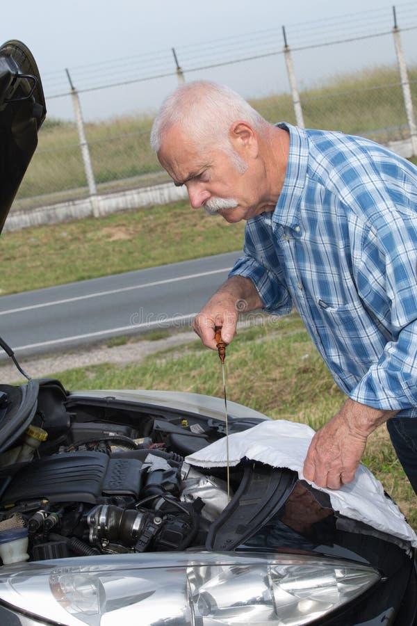 Stary mężczyzna sprawdza poziomy i obsługowego samochód zdjęcie royalty free