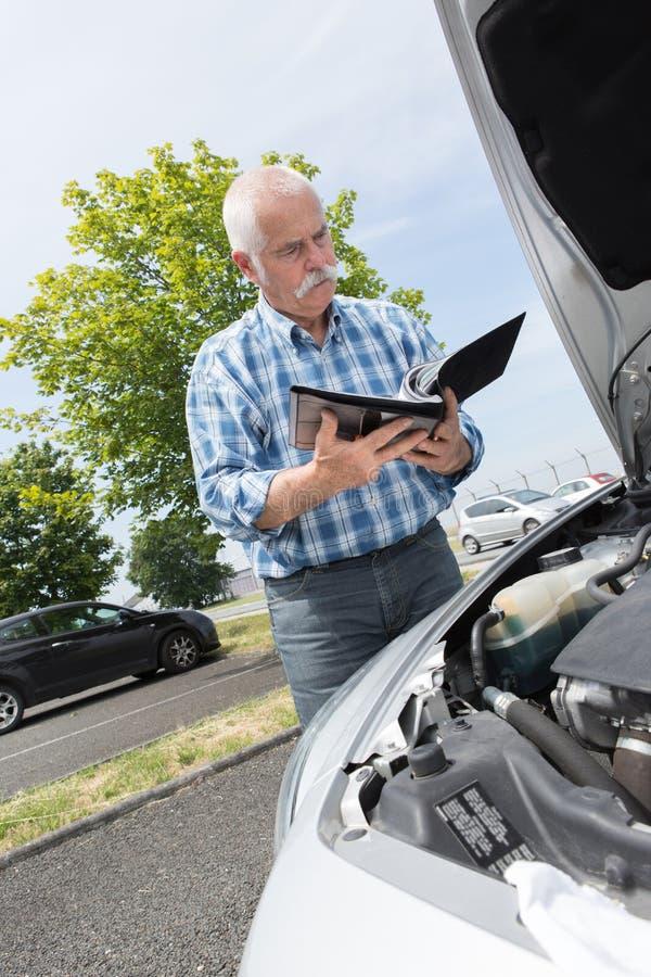 Stary mężczyzna sprawdza poziomy i obsługowego samochód zdjęcia stock
