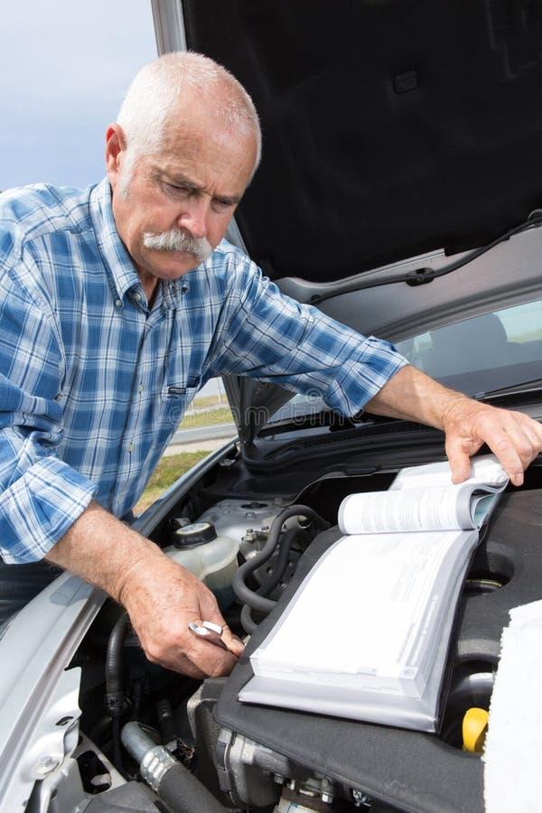 Stary mężczyzna sprawdza poziomy i obsługowego samochód fotografia royalty free