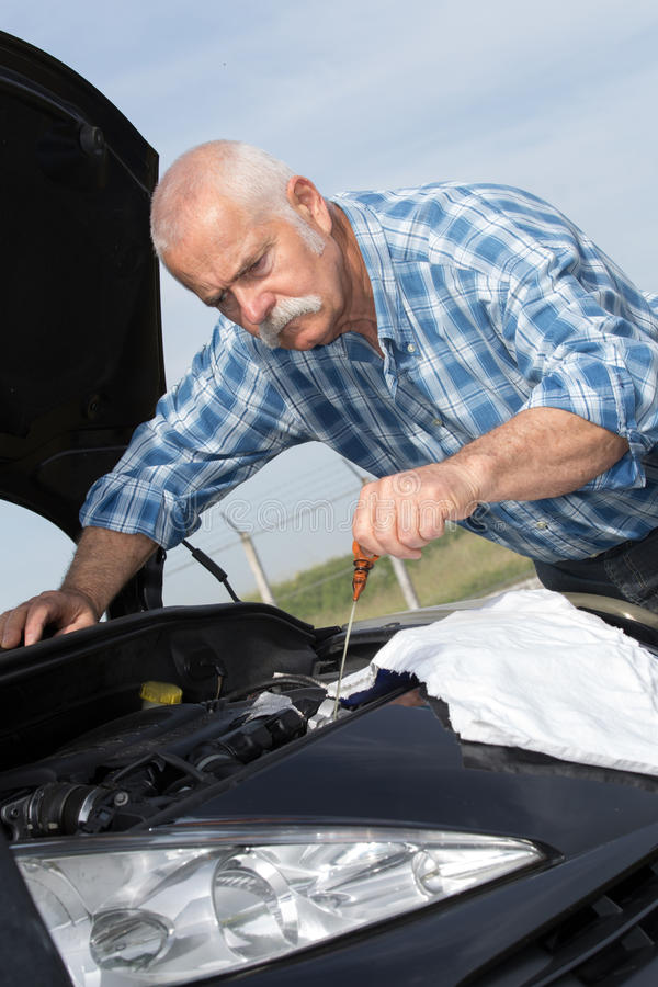 Stary mężczyzna sprawdza poziomy i obsługowego samochód zdjęcie stock