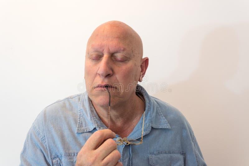 Stary mężczyzna trzyma szkła z oczami zamykał rozważnego, łysy, alopecia, chemoterapia, nowotwór obraz royalty free