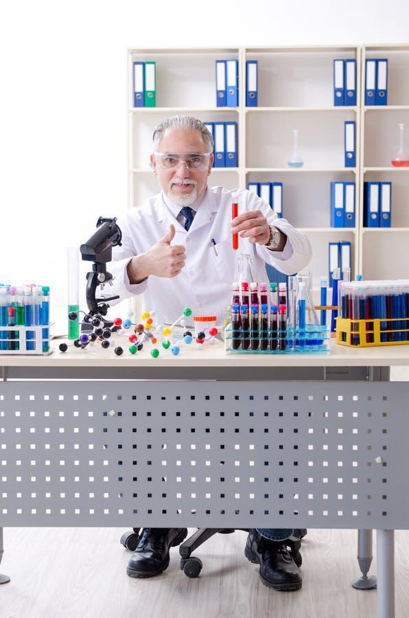 Stary m?ski chemik pracuje w lab obraz stock