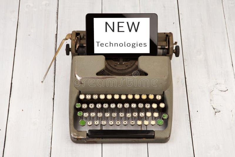 stary maszyna do pisania i nowy pastylka komputer osobisty z słowami & x22; NOWY Technologies& x22; zdjęcie royalty free
