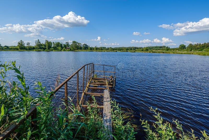 stary metalowy most w błękitnym jeziorze latem fotografia stock