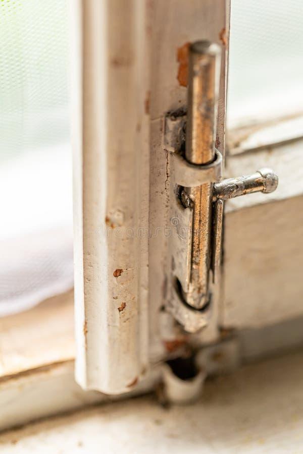 Stary metalu kędziorek na białej drewnianej nadokiennej ramie Stara drewniana nadokienna rama z małym ośniedziałym kędziorkiem fotografia stock