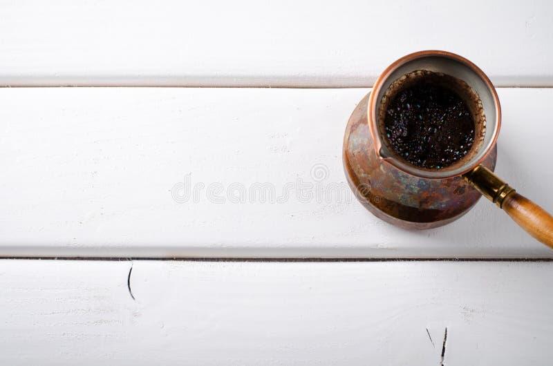 Stary miedziany kawowy garnek na białym drewnianym tle obrazy royalty free