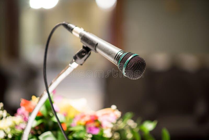 Stary mikrofon na zamazanym w seminaryjnego pokoju lub sala konferencyjnej tle fotografia royalty free
