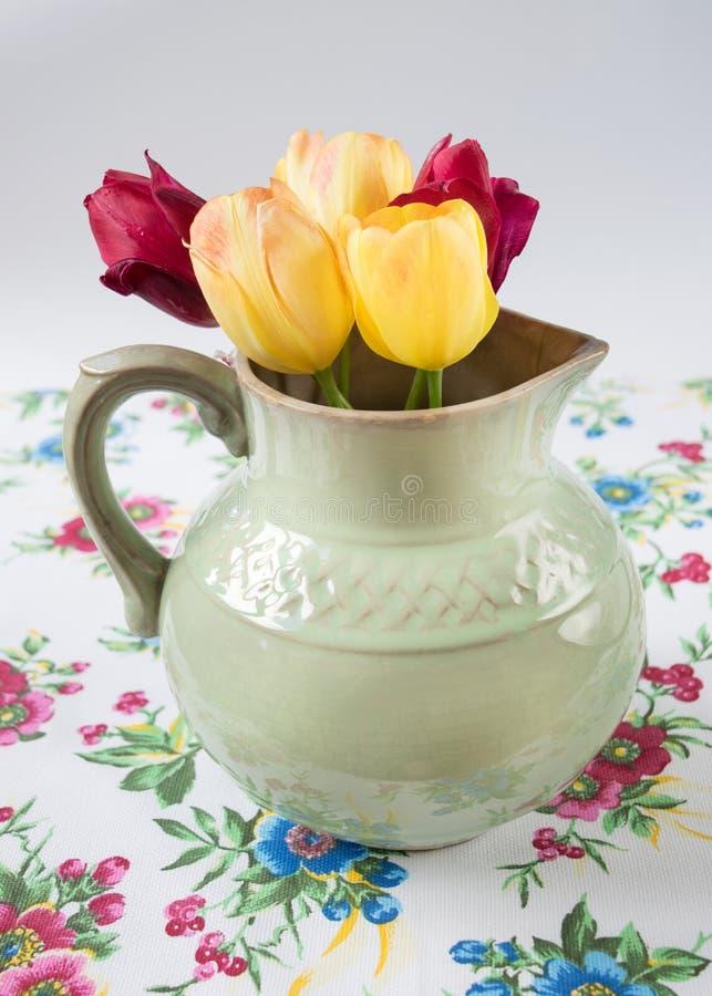 Stary miotacz z kwiatami tulipany obraz royalty free
