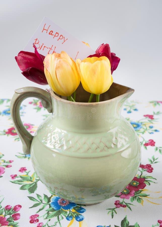 Stary miotacz z kwiatami tulipany obrazy stock
