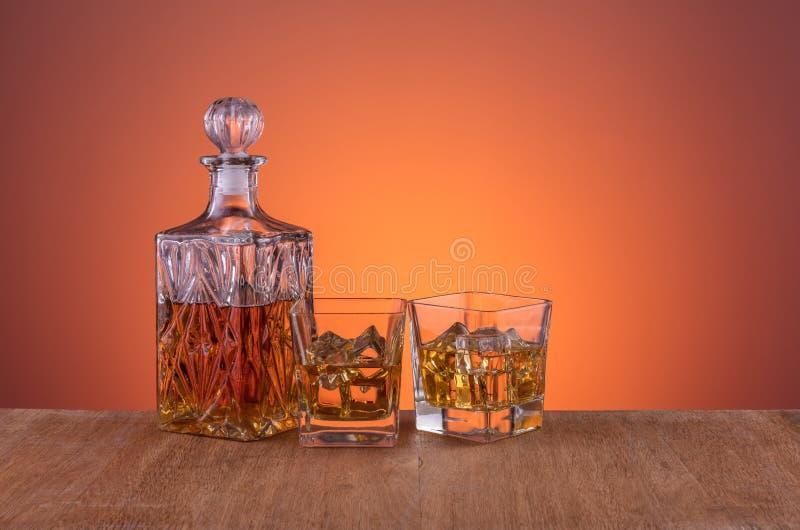 Stary mody szk?o, karafka z whisky i pijemy na tle i drewnie ciep?ym, pomara?czowym, zdjęcia stock