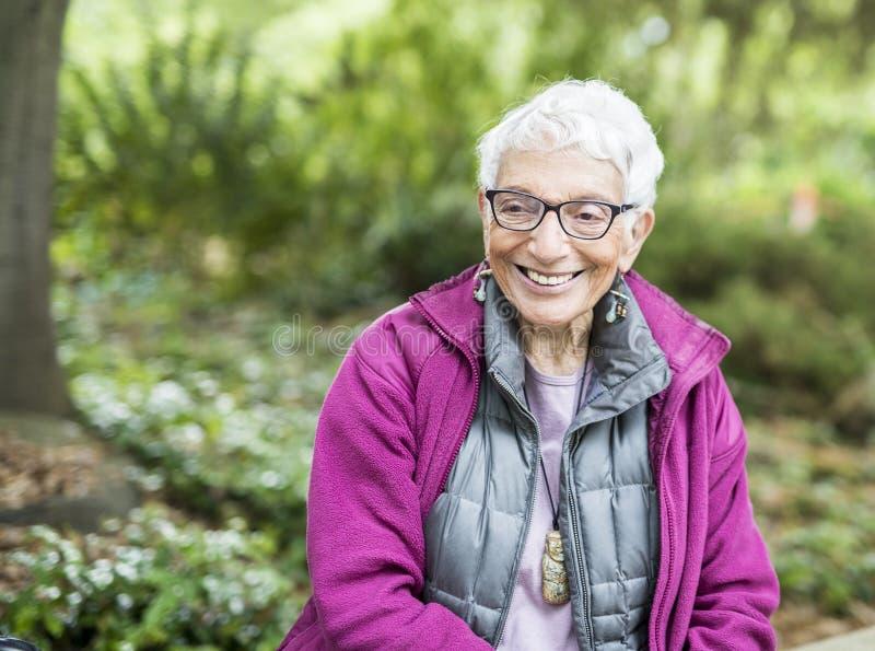 Stary Niezależny kobiety obsiadanie w Parkowy Uśmiechnięty & Szczęśliwym zdjęcia stock