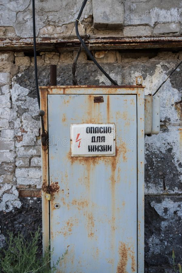 Stary ośniedziały drzwi za znakiem ostrzegawczym w zaniechanym rujnującym budynku zdjęcia stock