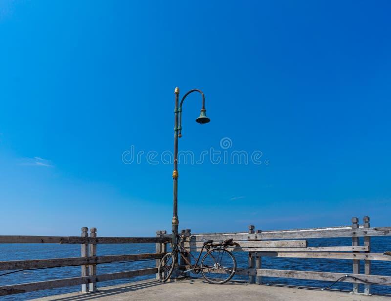 Stary Ośniedziały bicyklu park Pod Awaryjnym Lamppost Przy Drewnianym molem Marina Obok morza obraz royalty free