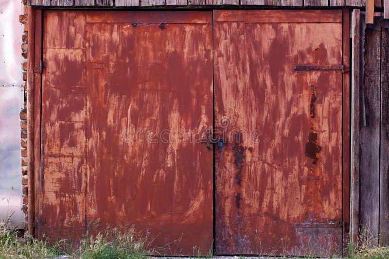 Stary, ośniedziały czerwony dwoisty drzwi, bezpiecznie zamykający obraz stock