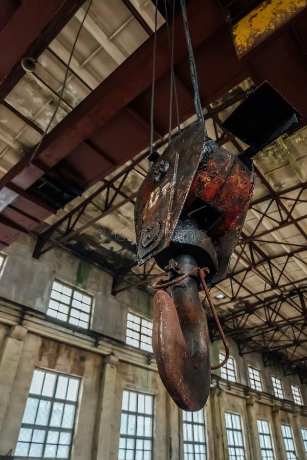 Stary ośniedziały dźwigowy haczyk wśrodku przemysłowego budynku obrazy royalty free