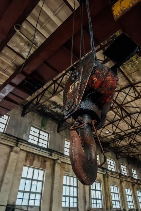 Stary ośniedziały dźwigowy haczyk wśrodku przemysłowego budynku zdjęcie stock