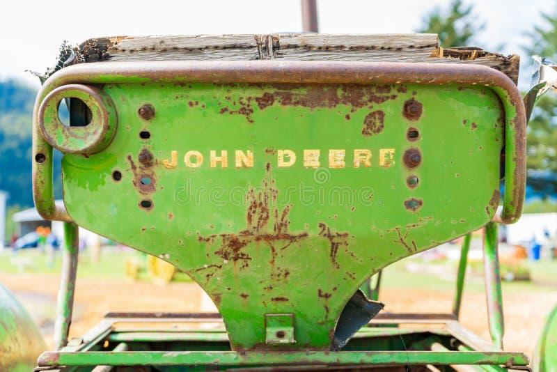 Stary, ośniedziały John Deere ciągnikowy siedzenie, pokazuje słowo oceny logo na plecy, będącym ubranym za Klasyczny John Deere w obraz stock