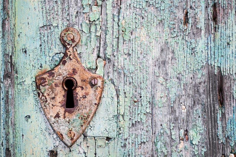 Stary ośniedziały metalu kędziorek, keyhole na starym turkusowym drewnianym drzwi i zdjęcia stock