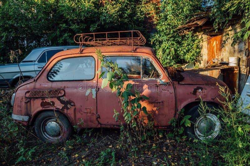 Stary ośniedziały przerastający zaniechany czerwony sowiecki retro samochód obraz stock