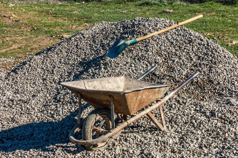 Stary ośniedziały wheelbarrow do góry nogami na rozsypisku ziemia w placu budowy, budowa teren zdjęcie stock