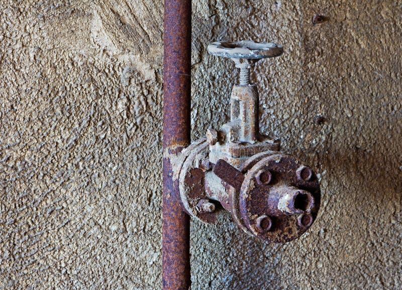 Stary ośniedziały wodny klepnięcie w betonowej ścianie obrazy stock