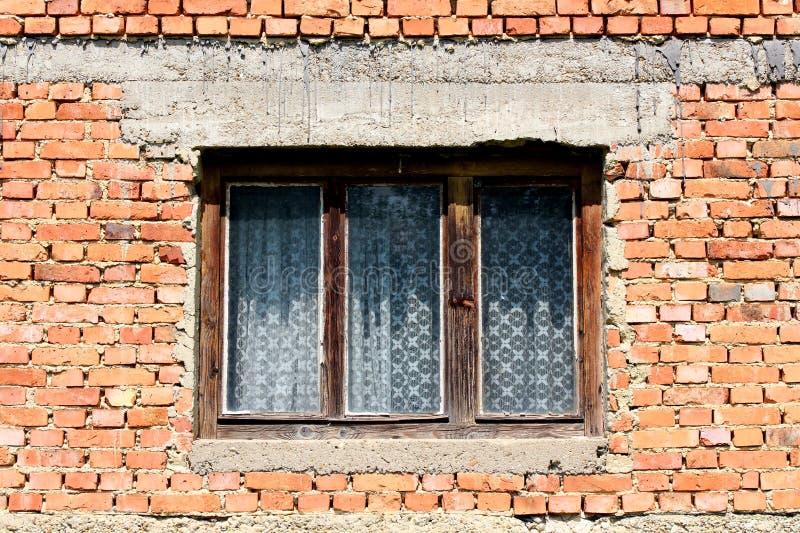 Stary obdrapany domowy okno z krakingową zatartą drewnianą ramą na czerwonej ścianie z cegieł fotografia royalty free