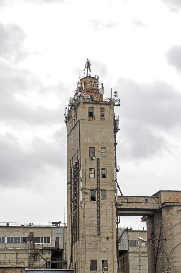 Stary, obdrapany, przemysłowy wieżowiec z komunikacyjnymi antenami na dachu, Rosja obrazy stock