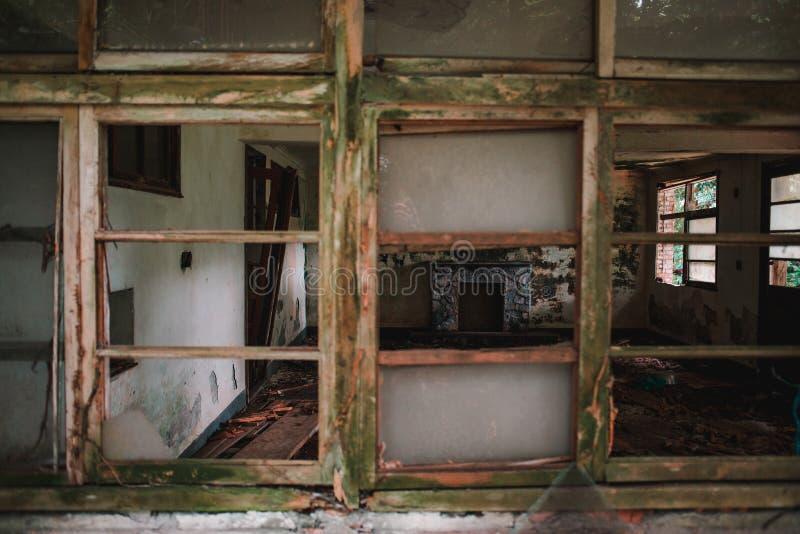 Stary opuszczony budynek z drewnianymi oknami i zniszczonymi murami - koncepcja zniszczenia fotografia stock