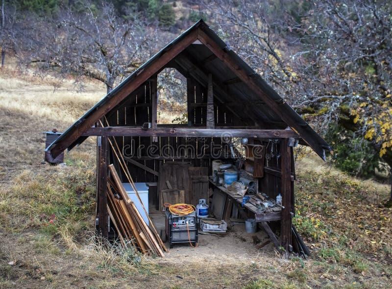 Stary otwiera frontową drewnianą jatę z generatorem, narzędzia i wypiętrzający drewno w wiejskim położeniu z drzewami za obrazy stock