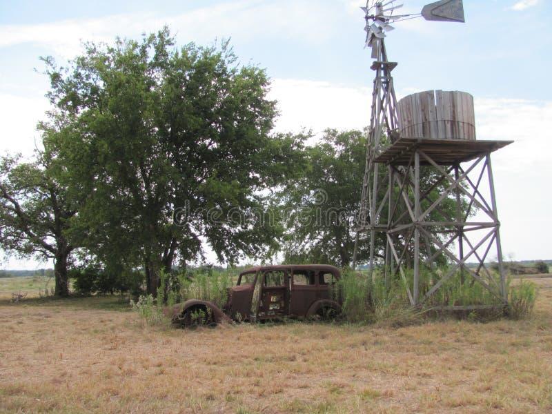 Stary północny Teksas gospodarstwa rolnego comp; ete z wiatraczkiem i starym 1930 ` s samochodem obrazy stock