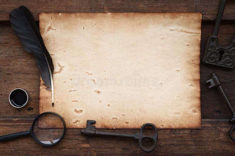 Stary papier na brown drewnianej teksturze z kluczem, piórkiem i atramentem powiększa, - szkło obrazy stock