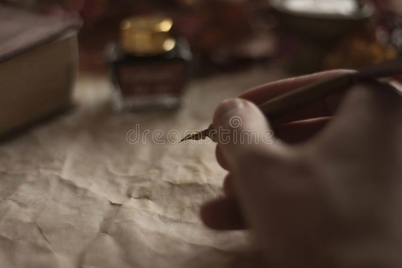 Stary papier z pisze ręką z piórkowym piórem, atrament i biblia na drewnianym stole obraz royalty free