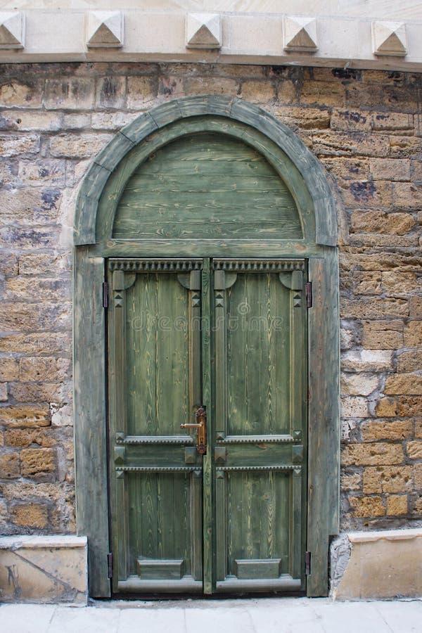Stary piękny zielony drewniany drzwi w kamiennej ścianie obrazy royalty free