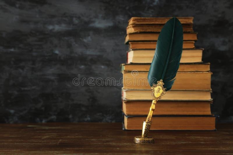 Stary pi?rkowy dutka atramentu pi?ro z inkwell i stare ksi??ki nad drewnianym biurkiem przed czerni? izolujemy t?o Rocznika stary zdjęcia royalty free