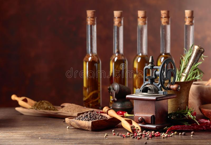 Stary pieprzowy m?yn z kulinarnymi naczyniami, butelkami oliwa z oliwek, pikantno?? i rozmarynami na drewnianym stole, zdjęcie stock