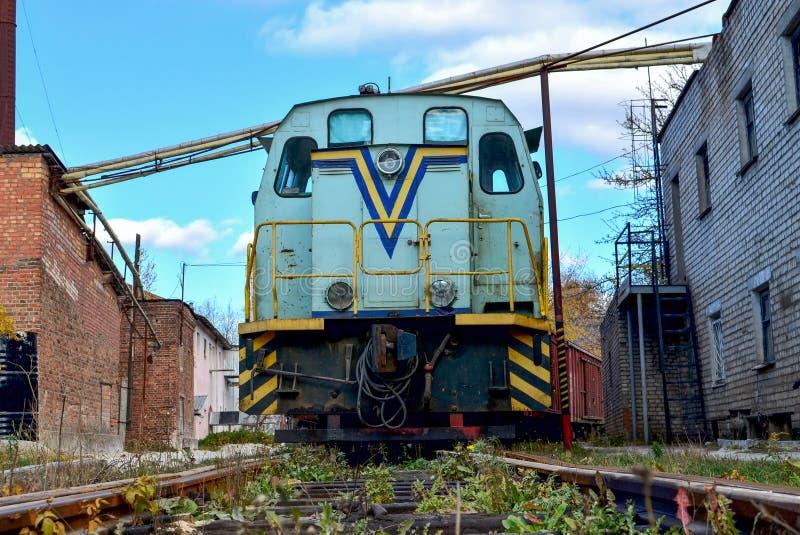 Stary pociąg, dieslowskiej lokomotywy stojaki na poręczach z frachtowymi samochodami w strefie przemysłowej roślina lub zajezdnia obraz royalty free