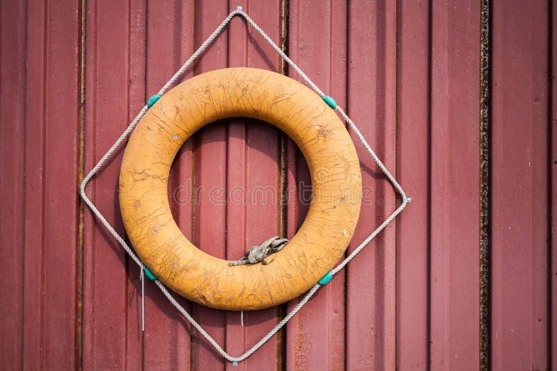 Stary pomarańczowy lifebuoy na czerwieni ścianie zdjęcia stock