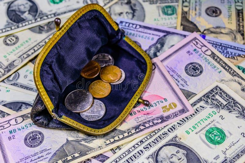 Stary portfel z amerykańskimi cent monetami nad dolarowymi banknotami zdjęcia stock