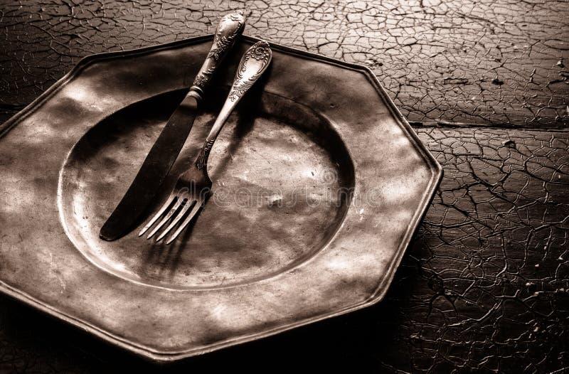 Stary powyginany nieociosany pewter talerz z cutlery obrazy royalty free