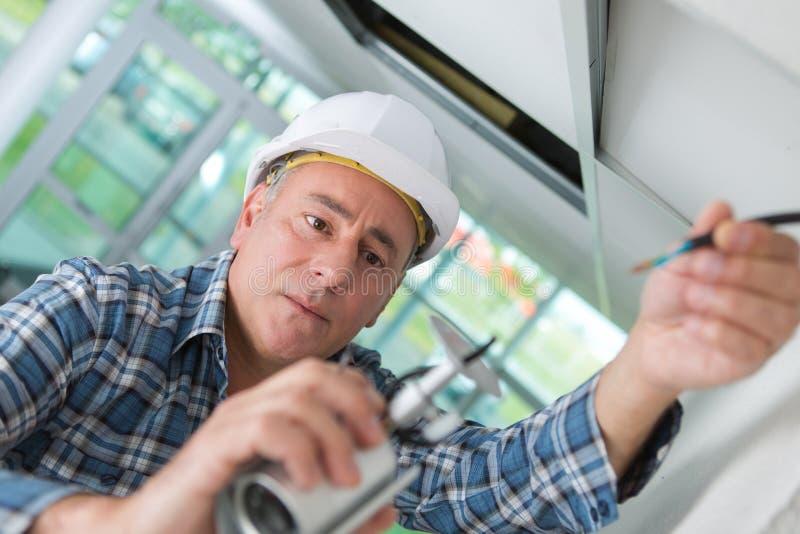 Stary pracownik w białym kask naprawiający fotografia royalty free