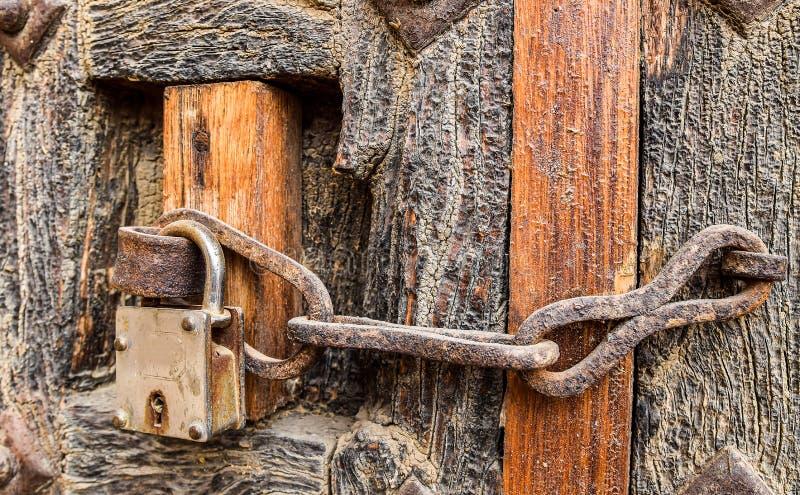 Stary projektujący ośniedziały łańcuszkowy drzwiowy kędziorek na drewnianym drzwi zdjęcie stock